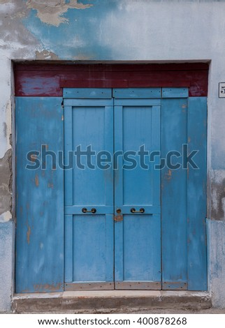 Old wooden locked blue door in light blue wall with peeling paint (Burano island, Venice , Italy)