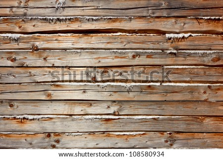 Old wooden logs with heat insulation material between them. Part of wooden house walls - stock photo