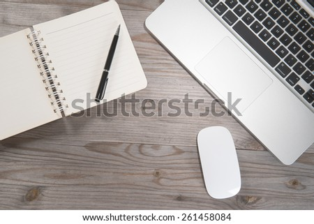 Old wooden office table with notepad, laptop and mouse. View from above with copy space. - stock photo