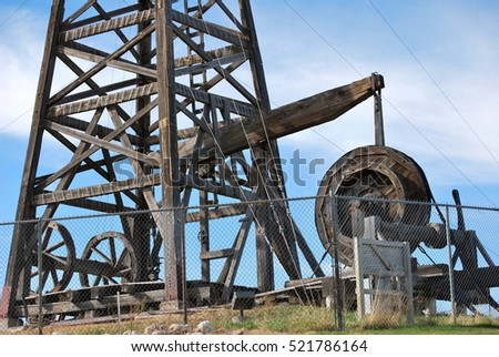 Old wooden oil rig displayed outdoors.