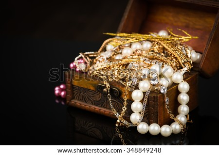 Old wooden open chest with golden jewelry on black background - stock photo
