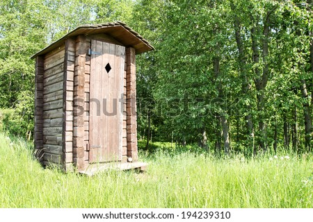 Old wooden outhouse for tourists at a forest  - stock photo