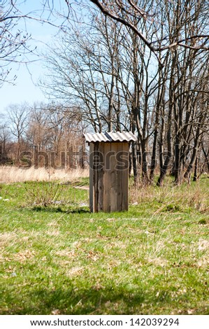 Old wooden outhouse in the forest. Bright spring day. - stock photo