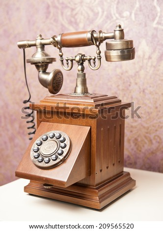 Old wooden phone. Vintage wooden telephone on white table. Retro phone. - stock photo