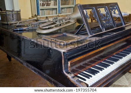 Old wooden piano in vintage finish with trumpets and drums - stock photo
