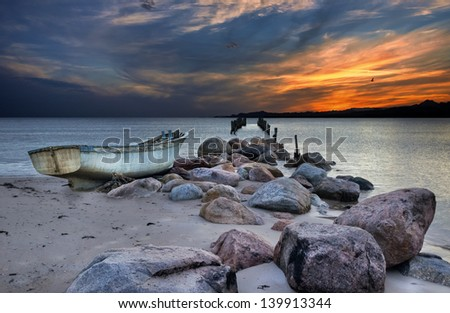 Old wooden pier and fishing boat after storm - stock photo