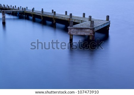 old wooden pier in water at sunset in Groningen, Netherlands