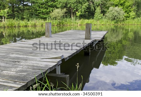old wooden pier jutting out into lake - stock photo