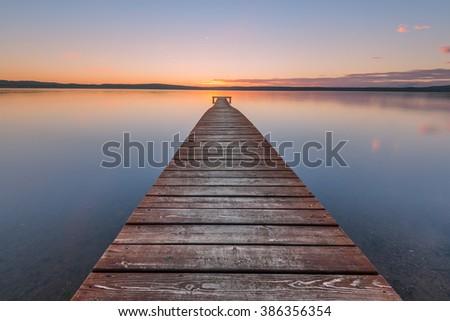 Old wooden pier on sunset - stock photo