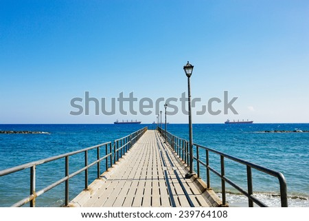 Old wooden pier over the Mediterranean sea shore in bright summer day. Limassol, Cyprus. - stock photo