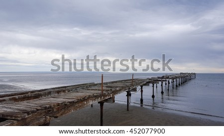 Old wooden pier  with cloudy and rainy day at the Punta Arenas beach, Chile