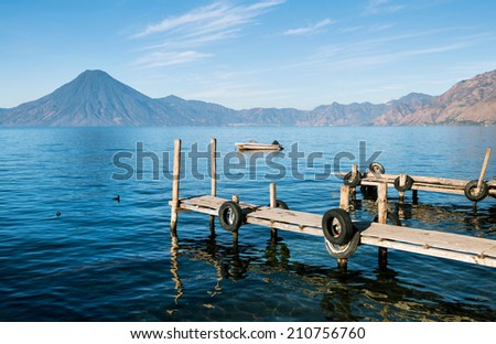 Old wooden piers and the boat on the lake Atitlan in Guatemala with volcano on the background  - stock photo