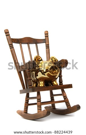 Old Wooden Rocking Chair And Golden Piggy Bank On White