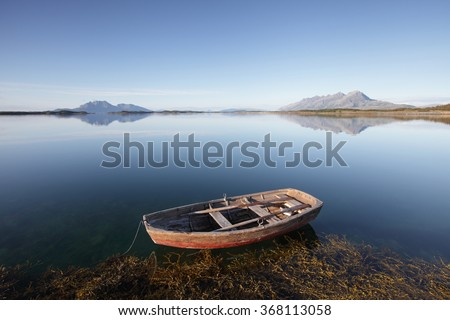 Old wooden rowing boat at Norwegian coast at clear sunny day, with mountains at horizon. Photographed at Helgeland, Nordland, Norway.