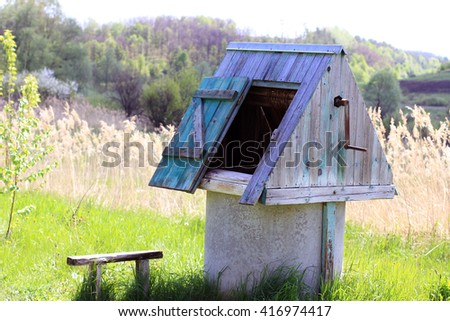 Old wooden rustic water well light blue color (draw well, rustic pit, rotten water well) and vintage bench rural scenery, forest, fields, sky, natural calm background