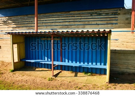 Old wooden seats on outdoor stadium players bench, chairs with worn paint below rusty metal sheets roof. Autumn poor grass, end of football season. - stock photo