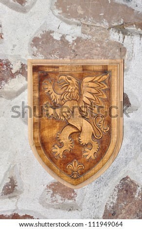Old wooden shield on a brick wall - stock photo