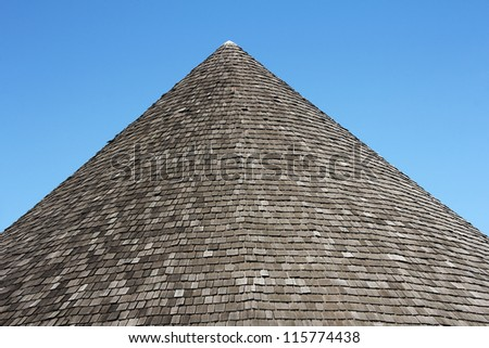 Old wooden shingle roof in the shape of a pyramid - stock photo