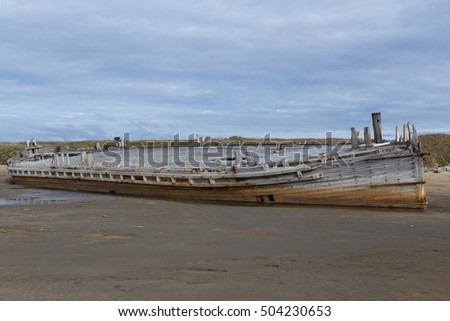 Old wooden ship stranded on a sandy beach. Laptev sea. Yakutia. Russia.
