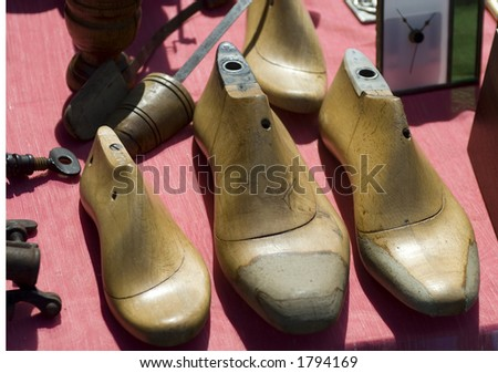 Old wooden shoe strechers lined up in a row on a table