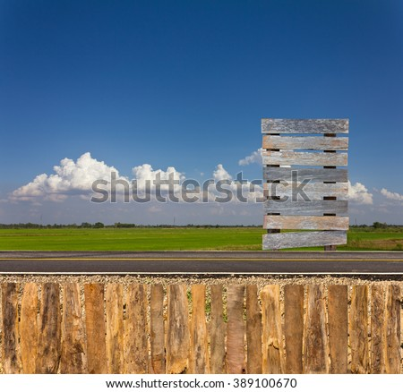 Old wooden sign beside the road in the countryside with a wooden fence and the sky as a backdrop. - stock photo