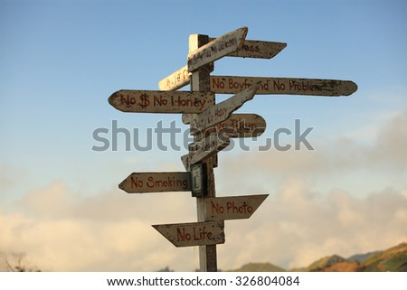 Old wooden sign with left and right arrows in the evening - stock photo