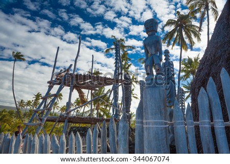 Old wooden structures and protection idols at ancient Hawaiian site Puuhonua O Honaunau National Historical Park on Big Island, Hawaii