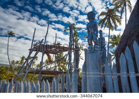 Old wooden structures and protection idols at ancient Hawaiian site Puuhonua O Honaunau National Historical Park on Big Island, Hawaii - stock photo