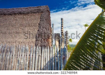 Old wooden structures with thatched roofs and protection idols at ancient Hawaiian site Pu'uhonua O Honaunau National Historical Park on Big Island, Hawaii - stock photo