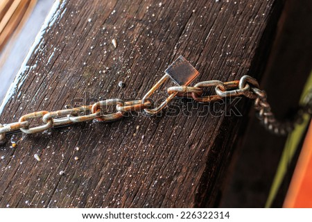 old wooden surface with chains and lock, concept of security  - stock photo