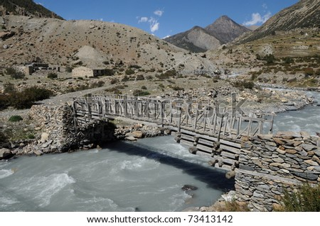 Old wooden suspension bridge over river in mountains, Himalaya, Nepal - stock photo