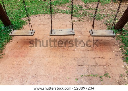 Old wooden swing on the playground in the park - stock photo