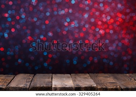 Old wooden table from weathered planks with glowing bokeh lights on background - stock photo