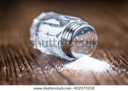 Old wooden table with a Salt Shaker (close-up shot; selective focus) - stock photo