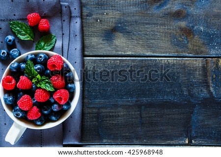 Old wooden table with assortment berries blueberries and raspberries at textile napkin over dark textured background. Top view composing with space for text. Flat lay. Rustic style. - stock photo