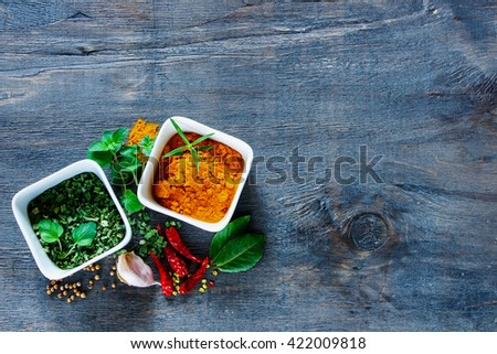 Old wooden table with dry herbs and spices selection (turmeric, paprika, rosemary, chives, pepper) on rustic background, top view, copy space. Dark rural style. - stock photo