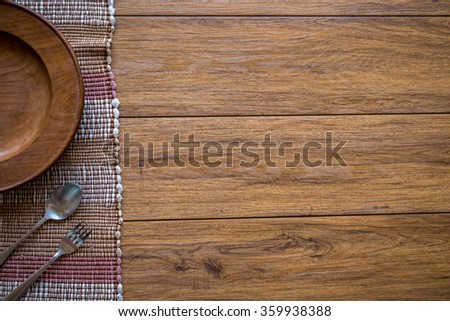 old wooden table with empty plate on a wooden table and copyspace good - stock photo