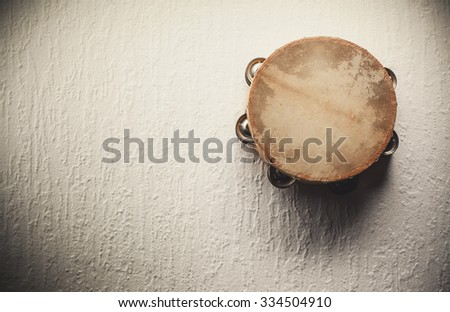 Old wooden tambourine hanged on the white wall.  - stock photo