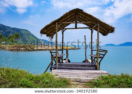 Old wooden terrace  on the shore of a tropical beach - stock photo