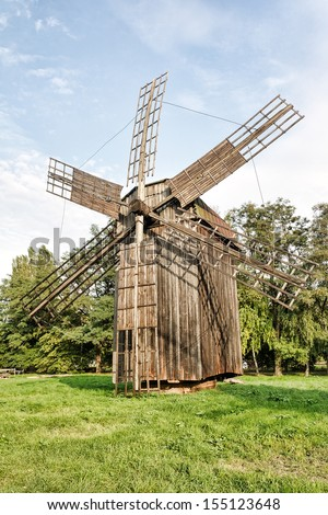 Old wooden traditional ukrainian windmill on green grass over blue sky with clouds