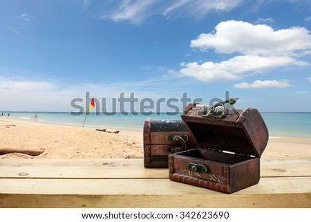 Old wooden treasure chest on the floor and beautiful beach and sky background - stock photo