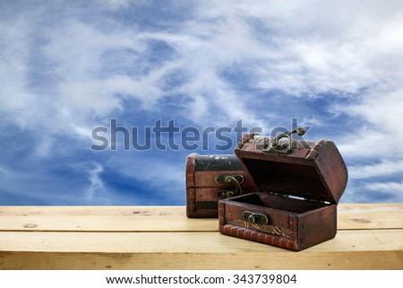 Old wooden treasure chest on the floor and beautiful  sky background - stock photo