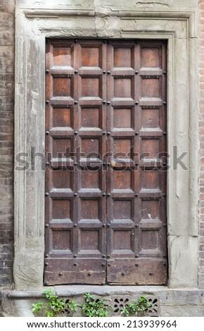 Old, wooden Tuscan door - stock photo