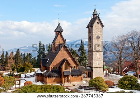 Old wooden Vang stave church with stone tower in Karpacz by winter, polish Karkonosze mountains.