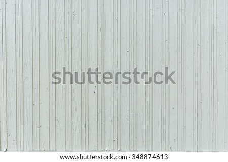Old wooden wall of vertical boards with white dried paint