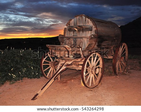Old wooden water-cart on a field, during the sunset
