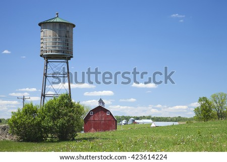 Old wooden water cistern and red barn in rural Iowa