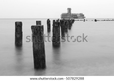 Old wooden waves breakers with in line with old torpedo testing building during Warld War II, Baltic Sea, Poland