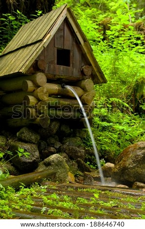 Old wooden well in an overgrown forest with falling water - stock photo
