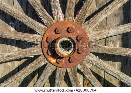 old wooden wheel with a rusty hub - stock photo